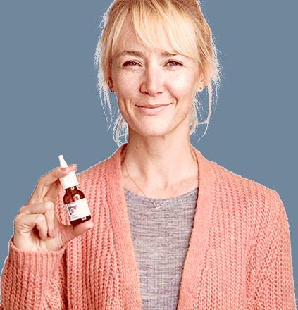 Frau mit Nasenspray in der Hand